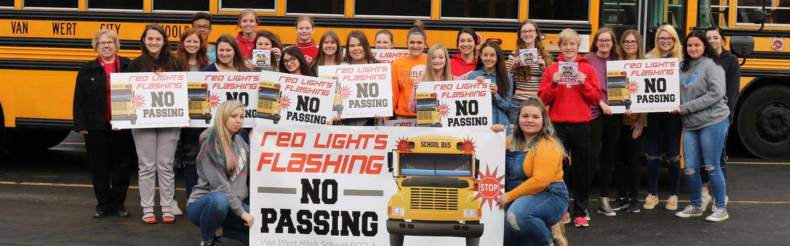 "FCCLA students pose beside school buses holding the signage they created for their bus safety campaign ""Red Lights Flashing No Passing"""