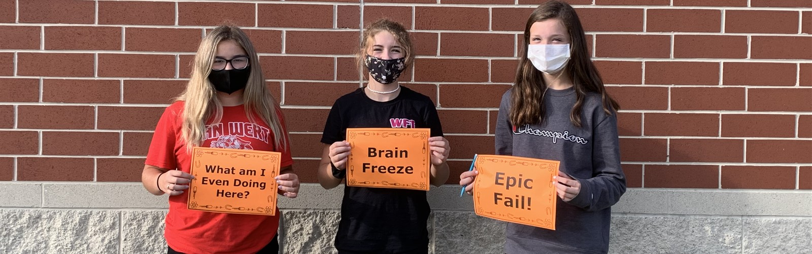 "Middle school girls who failed their escape room posed with signs saying ""What am I even doing here?"" ""Brain freeze"" and ""Epic fail!"""