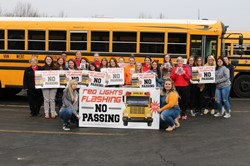 FCCLA stuents pose beside a bus with their banners and yard signs